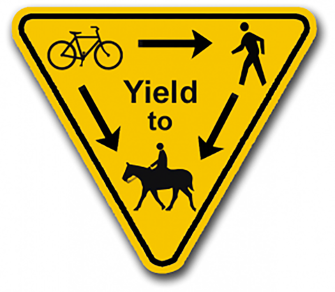 A sign with a picture of a person, a horse, and a bicycle, showing that all others yield to horses.